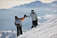 happy couple drivingand relaxing with snowboard and ski at winter seasson on mountain