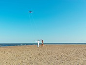 young couple playing with kite on seashore
