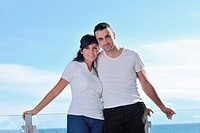 happy young couple relax on balcony outdoor with ocean and blue sky in background