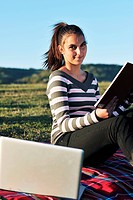 young teen girl read book and study homework outdoor in nature with blue sky in background