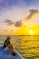 Woman in a ponga boat crossing the Sian Ka'an Biosphere Reserve at sunset, which is a small ecotourism and education center, it serves as a model for ...