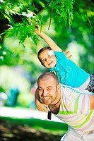 family father and son have fun at park on summer season and representing happines concept