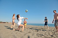 young people group have fun and play beach volleyball at sunny summer day