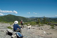 A hiker studies the landscape at the junction of Baldface Knob and Baldface Circle Trail in the White Mountains, New Hampshire USA during the spring m...