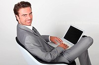 elegant businessman sitting in a chair and working on his laptop