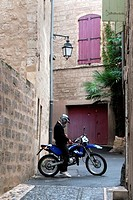 In a narrow street of the Renaissance town of Pezenas, a motor bike rider prepares to go