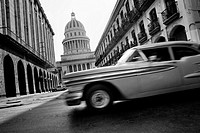 An American classsic car from the 1950s passing along the street in front of The Capitol El Capitolio, Havana, Cuba, 15 August 2008  El Capitolio is a...