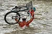 A Colombian gasoline smuggler carrying his bicycle in the middle of the river Táchira on the Colombian-Venezuelan border, 3 May 2006  The way the gaso...