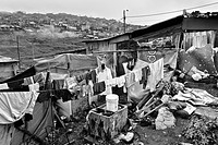 Washed clothes hung out to dry in the backyard of a wooden shack, a home of the internally displaced family, slum of Ciudad Bolívar, Bogota, Colombia,...
