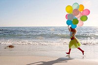 Young girl running along a beach with colorful balloons