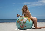 Woman in bikini leaning on globe