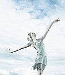 Dancer balancing in cloudy sky