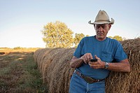 Farmer using cell phone by hay bales