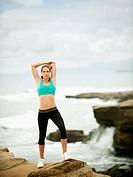 Caucasian woman stretching on rocks near ocean