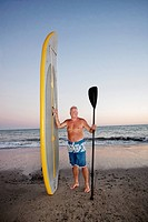 Caucasian man standing with paddleboard
