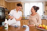 Hispanic nurse making tea for senior woman