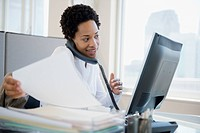 African American businesswoman using computer and talking on telephone