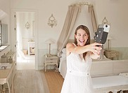 Woman using video camera in bedroom