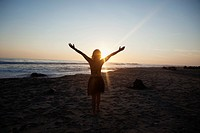 Girl with arms outstretched at sunset on the beach