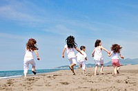 group of happy child on beach who have fun and play games