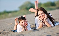 happy young mother and son relaxing and play ind sand games on beach at summer season