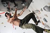 young and fit man exercise free mountain climbing on indoor practice wall
