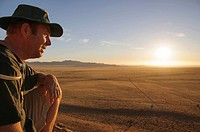 Hiker in safari hat looking at desert plain, Namib Desert, Aus, Karas, Namibia