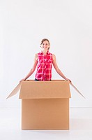 Studio shot of young woman inside box