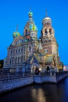 Kanal Griboedova and the highly ornate Church on Spilled Blood illuminated against a clear blue sky at dusk