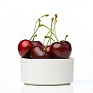 Big, ripe cherries, in a white bowl made of porcelain. The cherries are very fresh and have their stems. The whole concept has been shot on a white ba...