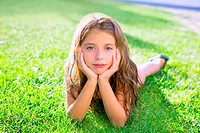 blue eyes children girl relaxed on the garden grass lying with hands in face