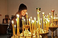 Woman lighting candles at Pechersk Lavra territory, Kiev, Ukraine