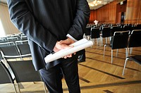 STOCKHOLM SWEDEN Businessman holding a plastic folder and document behind his back