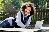 Schoolgirl lying on a bench with her laptop