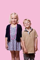 Portrait of happy brother and sister standing over pink background