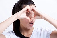 Young Asian woman making heart shape with hands against white background