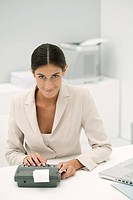 Woman using adding machine in office