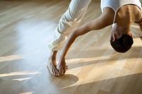 Woman doing prasarita padottanasana yoga pose, cropped