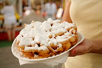 A woman holding a plate of funnel cakes covered in icing sugar at a market