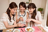 Three Young Women Looking Photograph with Digital Camera at Party