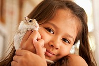 Mixed race girl holding small rodent