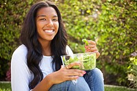 Mixed race girl eating edamame