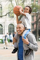 Black father and son playing basketball