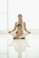 Hispanic woman practicing yoga with daughter in her lap