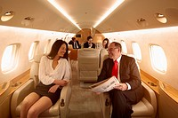 Business people flying on private jet