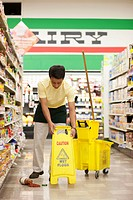 Mixed race man cleaning up spill in grocery store