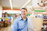 Caucasian man carrying bag in grocery store