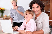 Parents and little girl with laptop