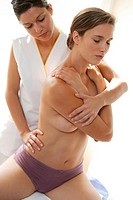 Back of a woman being manipulated by osteopath. Osteopathy uses massage and manipulation to treat a range of disorders, based on an understanding of t...
