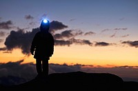 Aided by a headlamp a young boy enjoy the nighfall in the mountains